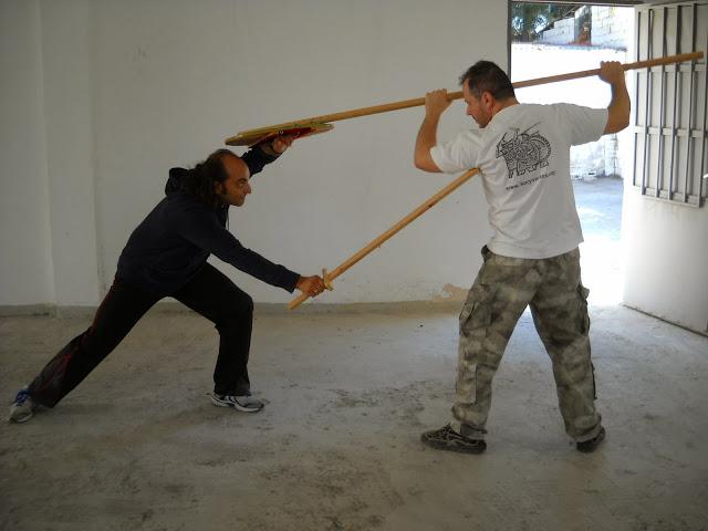 στις φωτ.Μάθημα οπλομαχίας ανάμεσα σε μαχητή που φέρει μικρή  ασπίδα και Βυζαντινού σπαθιού τύπου 'σπαθίον' ενάντια σε λογχοφόρο. Ο εξοπλισμός είναι μια ευγενική χορηγία του Συλλόγου Ιστορικών Μελετών 'ΚΟΡΥΒΑΝΤΕΣ'.